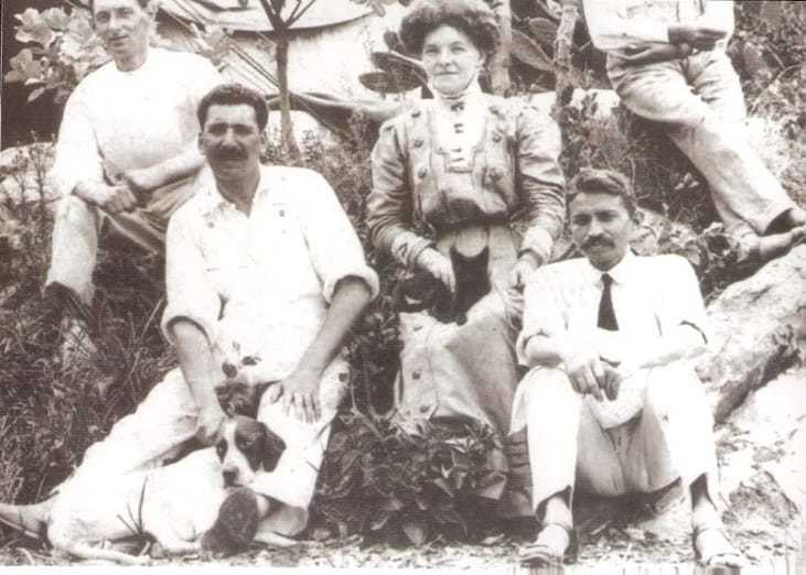 """Mahatma Gandhi, Dr. Hermann Kallenbach (with dog), Devadas Gandhi (Gandhi's son, right) and others in front of """"The Tent"""" at the living quarters orchards of Tolstoy Farm near Johannesburg, South Africa, ca. 1910"""