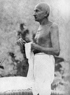Gandhi cleaning his spectacles, Wardha. 1939.