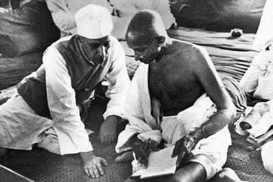 """Pandit Nehru and Mahatma Gandhi during the All-India Congress Committee session, Bombay, August 8, 1942, when the """"Quit India"""" resolution was adopted, calling for the immediate dissolution of British rule. The following morning, British authorities arrested Gandhi and Nehru, along with other top Indian political leaders. 8 August 1942."""