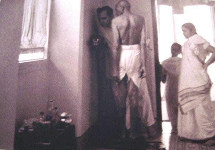 Mahatma Gandhi standing on a weighing scale at Birla House. Mumbai, 1945.