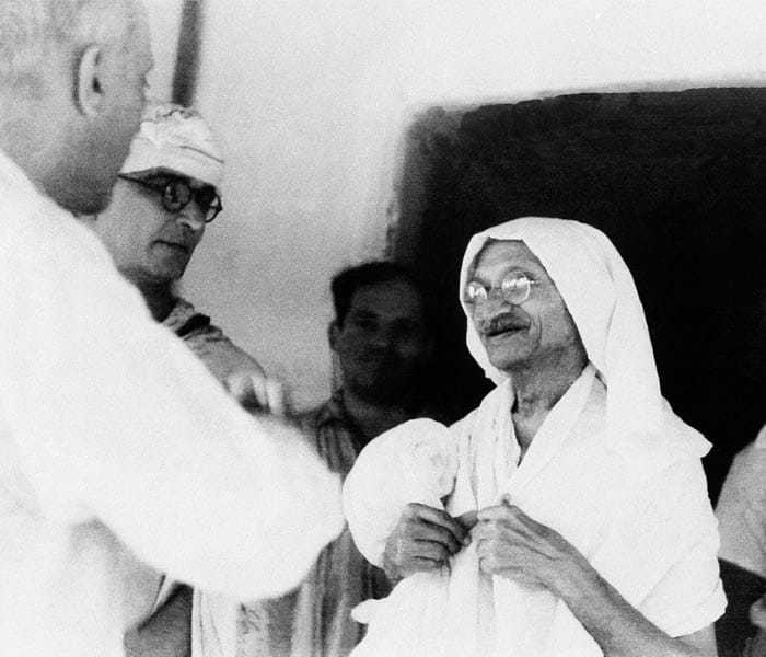 Mahatma Gandhi chatting with Jawaharlal Nehru in the doorway of the house where they conferred in Wardha, Bombay, September 9, 1942. At far left is Gandhi's secretary, Mahadev Desai.