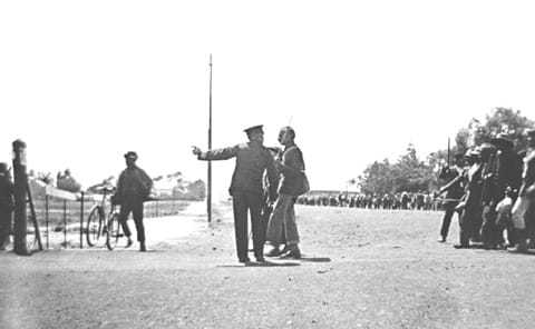 Policeman confronting Gandhi as he led the striking Indian, 1913