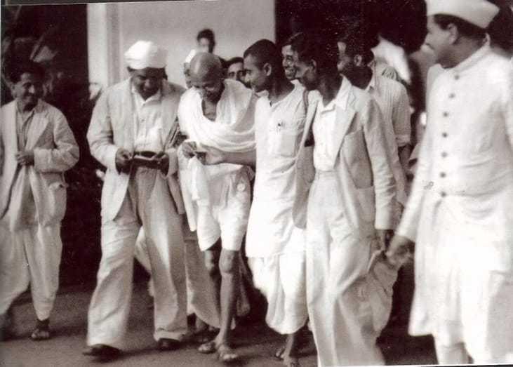Gandhi walking with Kanu Gandhi (right) and others. Mumbai. Maharashtra. India. September, 1944.