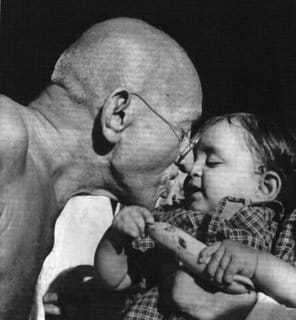 Mahatma Gandhi presenting a birthday present to Nandini, niece of Pyarelal Nayar at Sevagram Ashram. August 1944.