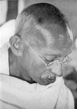Gandhiji inspecting the 'hook worms' through microscope during his convalesce at Jehangir Patel's hut in Juhu, Bombay. May 1944.