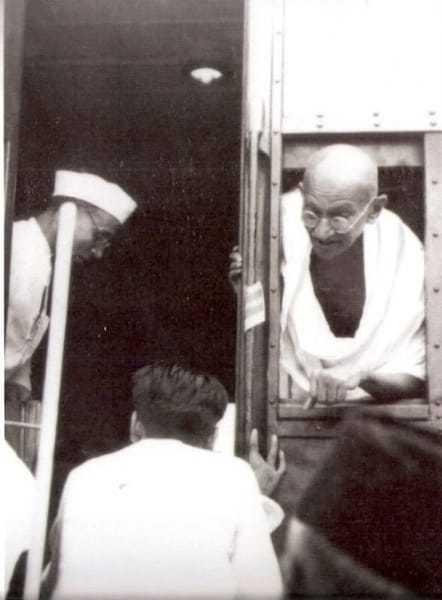 Gandhi during a train journey in 1945. Left his secretary Pyarela.