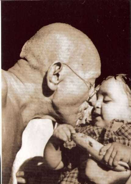 Mahatma Gandhi presenting a birthday present to Nandini, niece of Gandhi's secretary Pyarelal Nayer, at Sevagram Ashram, August 1944.