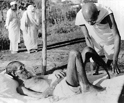 Gandhi giving massage, 15 min. daily, to a leper patient, the Sanskrit scholar Parchure Shastri, at Sevagram Ashram. 1940.