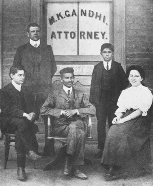 Mohandas Gandhi (center) sits with co-workers at his Johannesburg law office in 1902