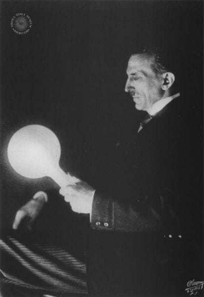 One of Dr. Tesla's striking experiments. A blare of light produced in a filamentless bulb by wireless power transmitted from a loop carrying terrific currents oscillating eighty million times per second.