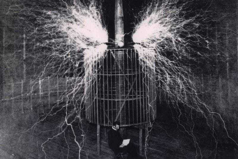 Burning the nitrogen of the atmosphere. This result is produced by the discharge of an electrical oscillator giving twelve million volts. The electrical pressure, alternating one hundred thousand times per second, excites the normally inert nitrogen causing it to combine with oxygen. The flame-like discharge measures sixty-five feet across. Tesla sits in front of the oscillator in a second exposure.