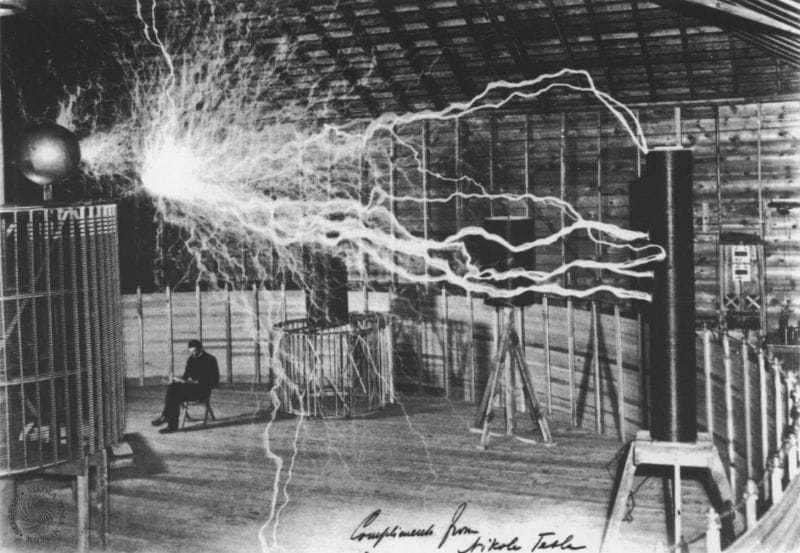 """This publicity photo taken at Colorado Springs was a double exposure. Tesla poses with his """"magnifying transmitter"""" capable of producing millions of volts of electricity. The discharge here is twenty-two foot in length. The inscription on the photograph is addressed to Sir William Crookes and reads; To my illustrious friend Sir William Crookes of whom I always think and whose letters I never answer. June 17, 1901 Nikola Tesla."""