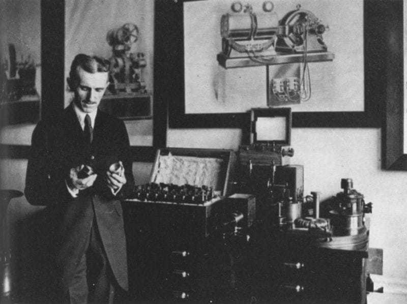 Tesla in his office in 1916, demonstrating an electrical apparatus.