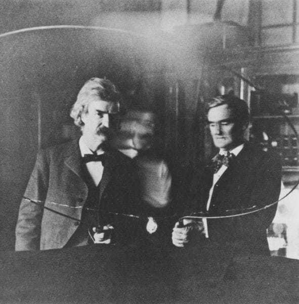 """Mark Twain and Joseph (""""Jo"""") Jefferson in Tesla's South Fifth Avenue laboratory, 1894, with blurred image of Tesla between."""