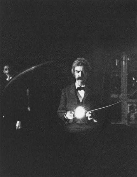The high-voltage high frequency current is being passed through the human body to bring the lamp to incandescence. Mr. Samuel Clemens (Mark Twain) is holding the loop over the resonating coil. Tesla is at the switch in the background. (From a flash-light photograph.)