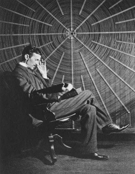 """Nikola Tesla, with Roger Boskovich's book, """"Theoria Philosophiae Naturalis,"""" in front of the spiral coil of his high-frequency transformer at East Houston St. 46, New York."""