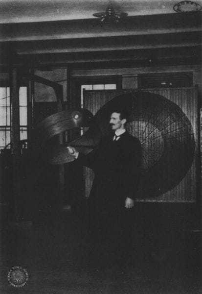 "Tesla demonstrates ""wireless"" power transmission in his Houston Street laboratory in March 1899."