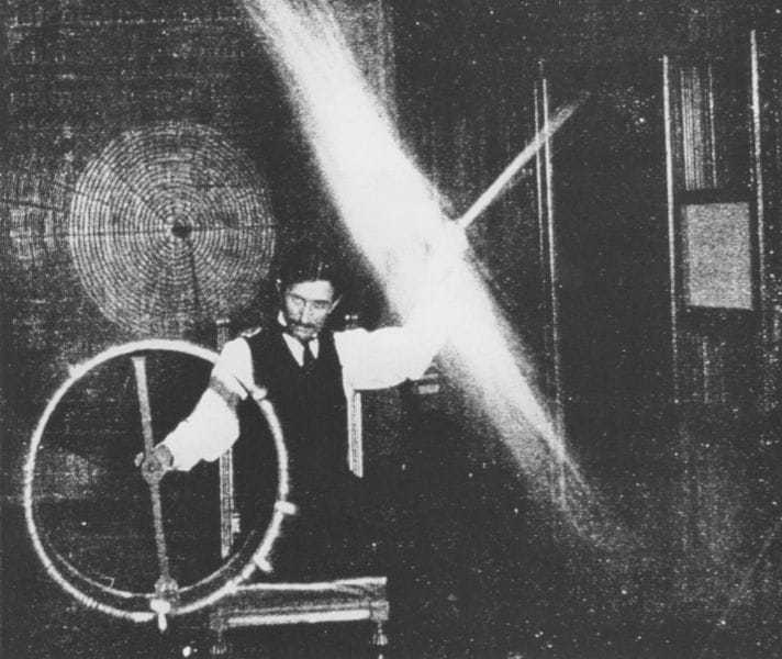 Tesla's body, in this experiment, is charged to a high potential by means of a coil responsive to the waves transmitted to it from a distant oscillator. A long glass tube waved in the hand is lighted to great brilliancy by the electrical charges conveyed to it through the body.