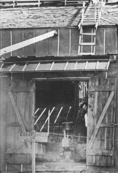 Tesla peaks out the door of the Colorado Springs laboratory, early summer 1899.