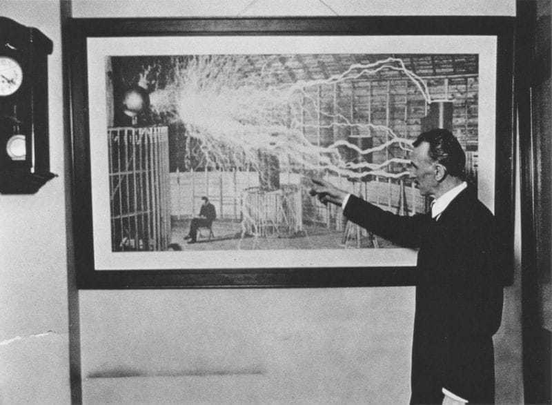 Tesla in 1916 pointing to a discharge in a photograph taken at Colorado Springs in 1899.