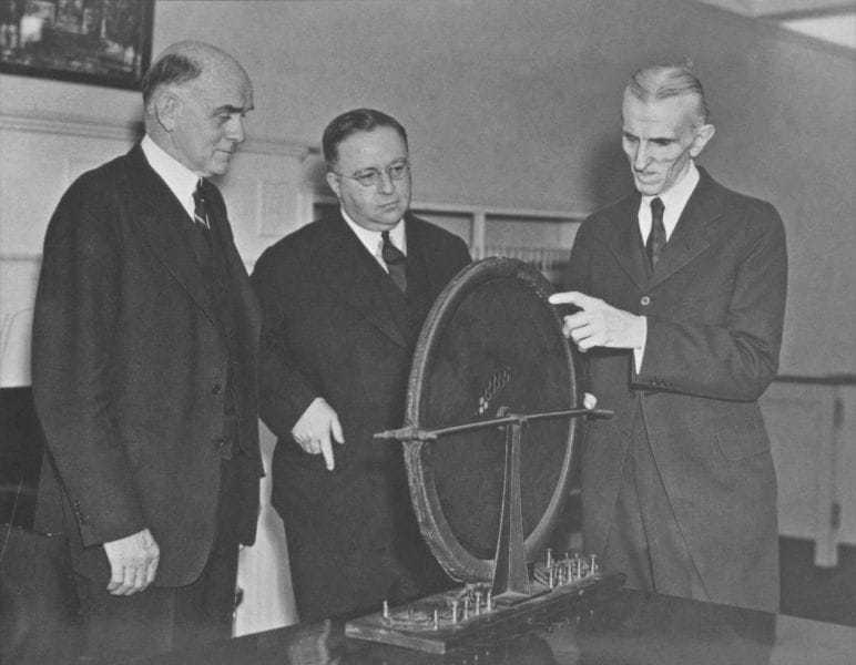 The first of three photos of Tesla in the office of Victor Beam (left), patent counsel, Westinghouse Electric & Manufacturing Company. The subject of the visit was an alternator that had escaped destruction in Tesla's laboratory fire in 1895. The Westinghouse Company had borrowed the alternator, but the fire disaster so absorbed Tesla's efforts in reestablishing his laboratory that the machine was forgotten.