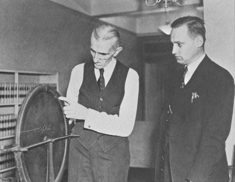 Photo two of three. Tesla and John T. Morris of the Westinghouse Electric & Manufacturing Company examine the alternator that had been discovered.