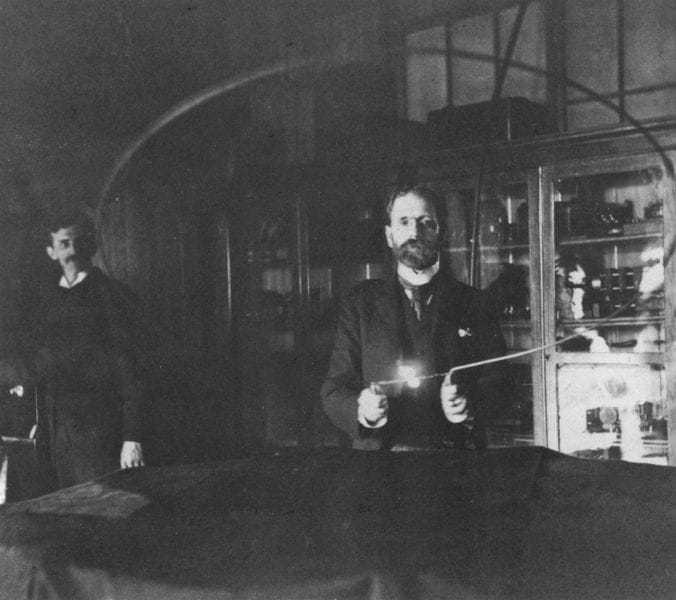 Robert Underwood Johnson holding a loop with an incandescent lamp. Tesla is in the background at the switch.
