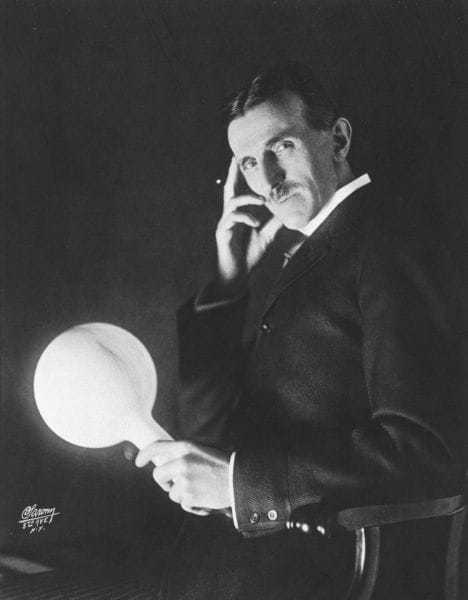 Tesla holding a gas-filled phosphor coated wireless light bulb which he developed in the 1890's, half a century before fluorescent lamps come into use. Published on the cover of the Electrical Experimenter in 1919.